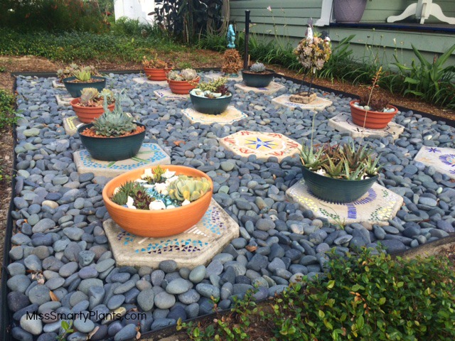 succulent container garden display area with stained glass stepping stones display area